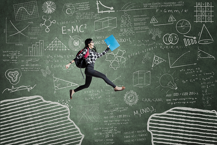 Happy student jumping in front of math on chalkboard
