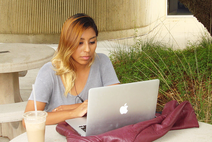 Woman sitting at a laptop outside