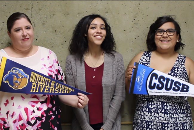 Three girls holding school pennants