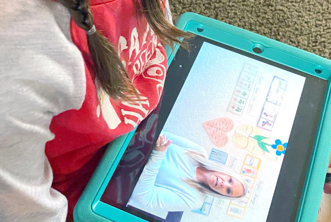 Child interacting with CDC teacher on a tablet