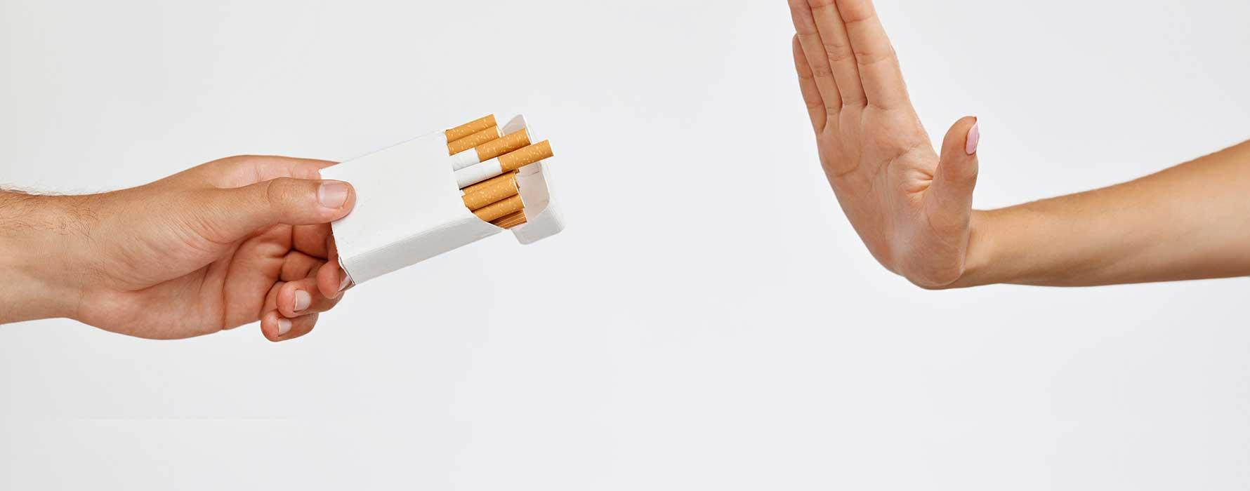 Hand offering cigarettes and another rejecting them