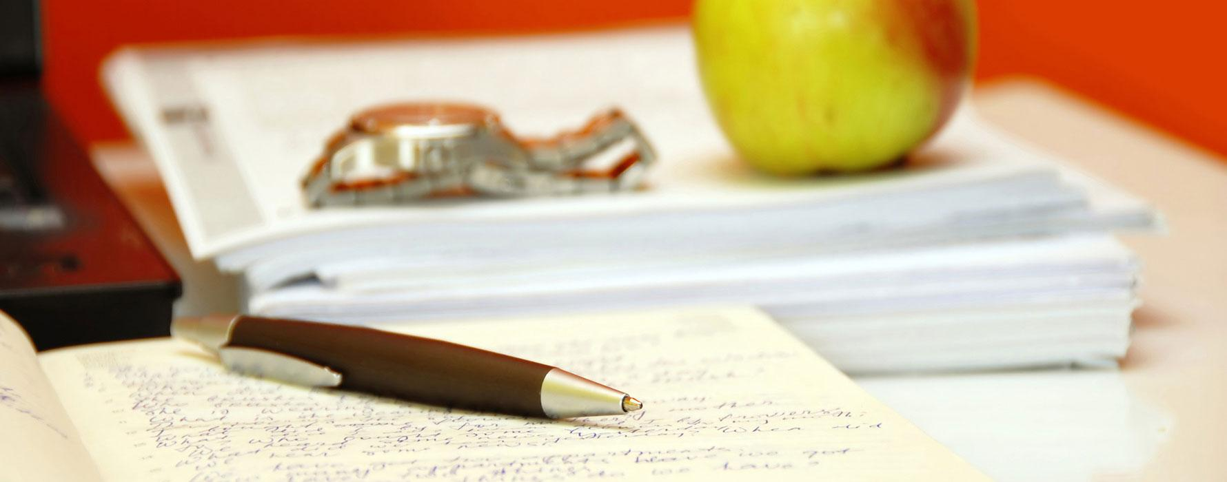 Apple, watch and pen on study notes
