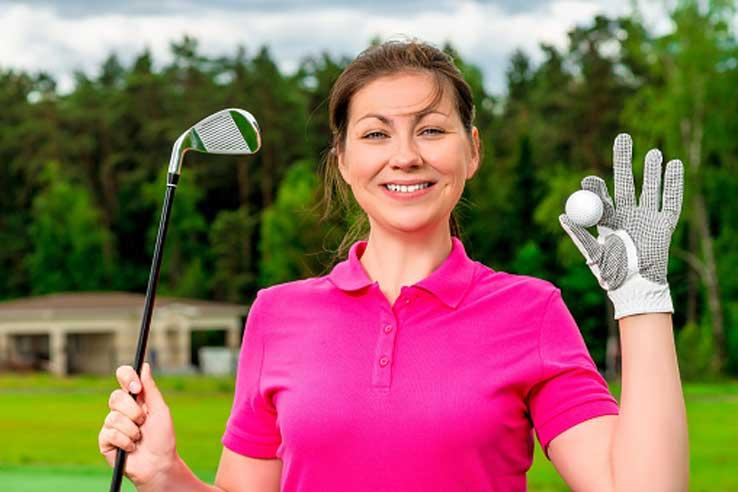 Woman holding golf club and ball
