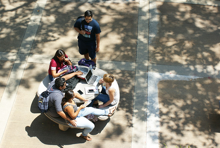 Aerial view of students sitting at a table on campus