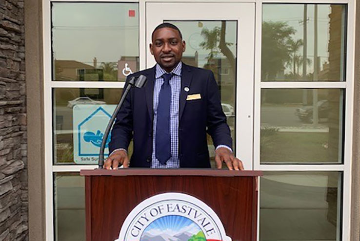 Ibraheem Lawal at the podium in front of the City of Eastvale City Hall building.