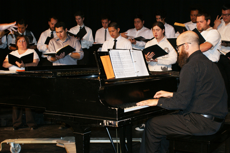 A group of students singing and playing piano.