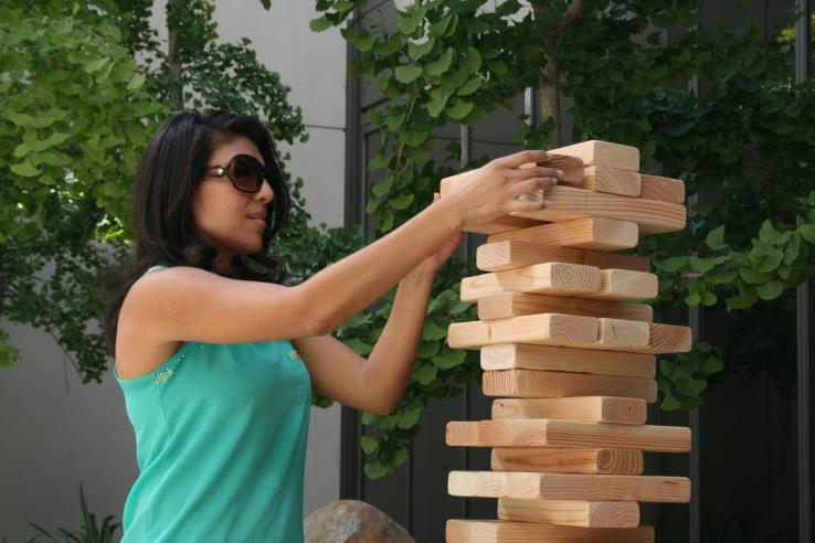 A person playing Giant Jenga.