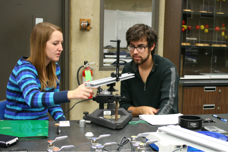 Students working with a machine in a lab