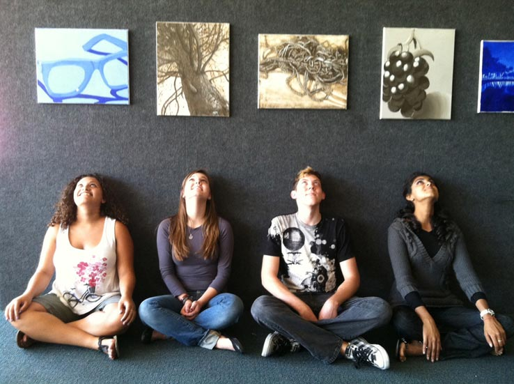 Students sitting beneath paintings displayed on a wall