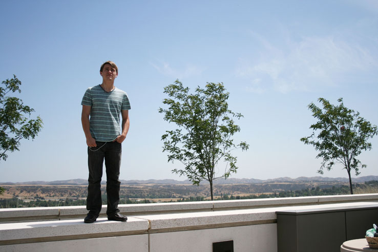 A student standing in front of a few small trees.