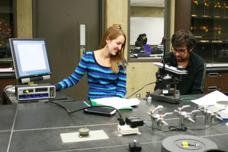 Two students doing a physics experiment.