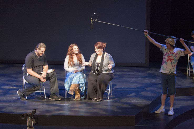 Three students acting on stage.