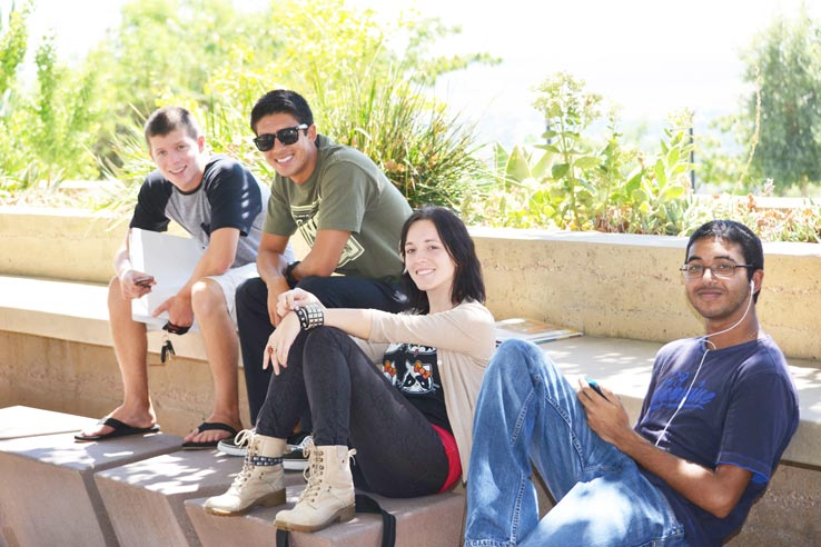 Four students sitting down together outside.