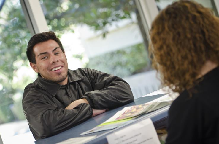 A student in the Admission and Records building talking with faculty.