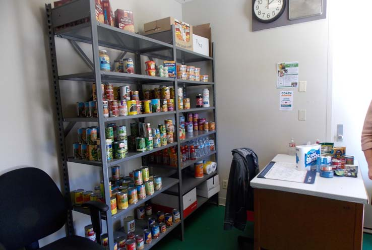 A shelf full of various food items and supplies in the COACH Cupboard room.