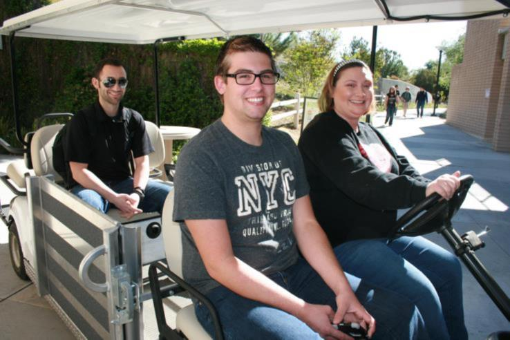 Three people in a golf cart outside of the Disabled Student Services building.