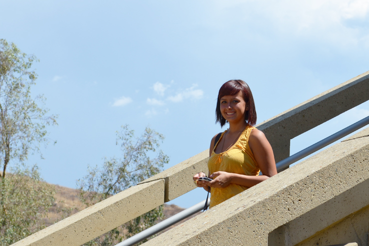 A female student smiling on a staircase.