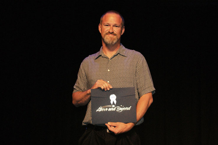 A man holding an award that says Above and Beyond