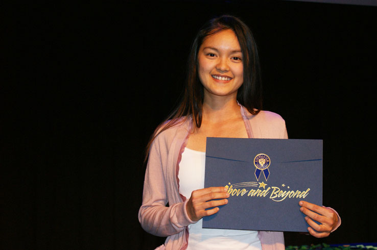 "Student holding up an elegant envelope bearing the words ""Above and Beyond"""