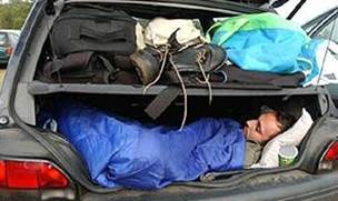 A person asleep in the trunk of a vehicle.
